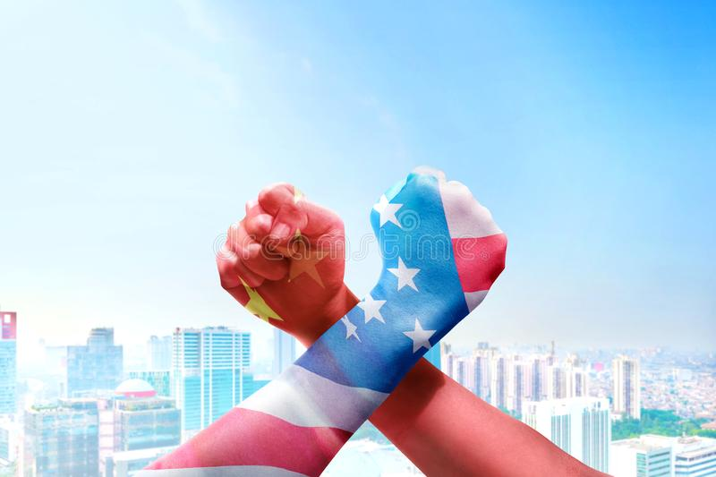 People with Chinese skin and American skin arm-wrestling. Over cityscapes background. Trade war Chinese against America stock photos