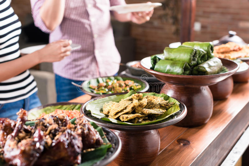 People choosing food at Indonesian buffet in restaurant stock images