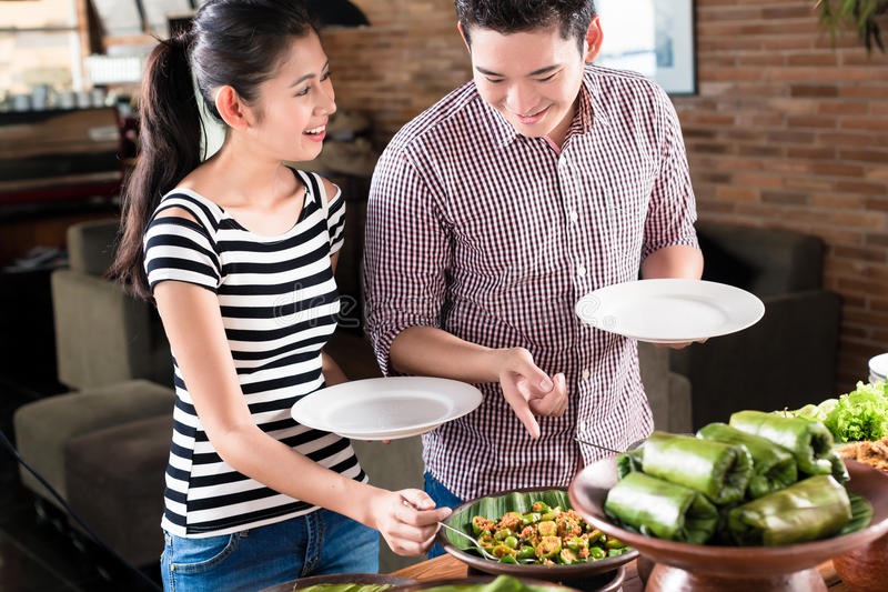 People choosing food at Indonesian buffet in restaurant. Asian women and men choosing food at Indonesian buffet in restaurant royalty free stock photo