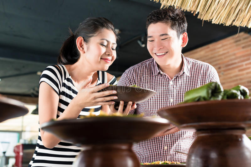 People choosing food at Indonesian buffet in restaurant. Asian women and men choosing food at Indonesian buffet in restaurant royalty free stock image