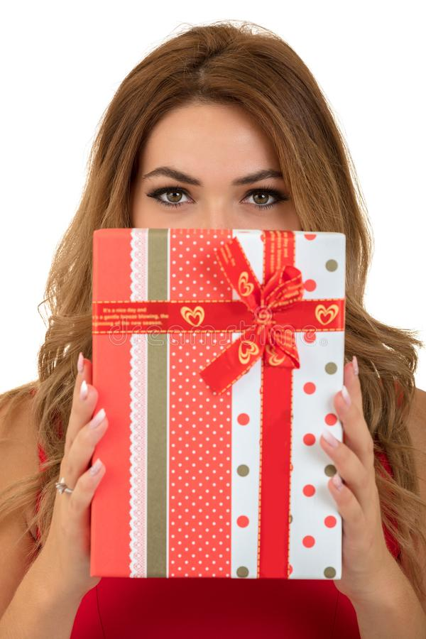 People, christmas, birthday and holidays concept - happy young woman in red dress playing with gift box stock image