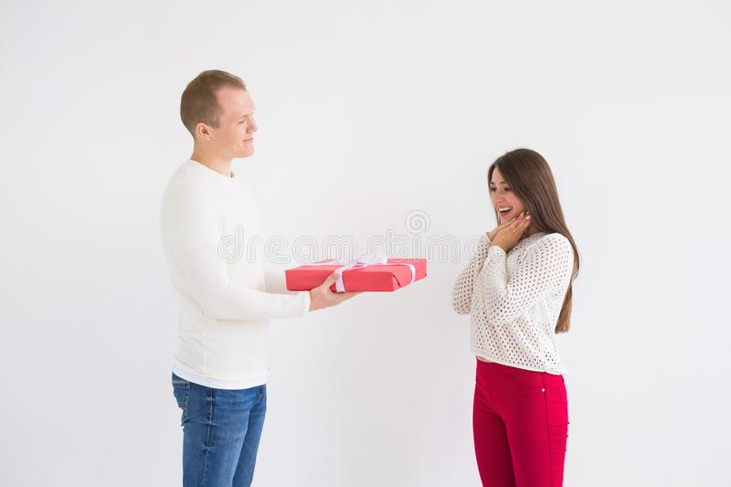 People, christmas, birthday, holidays and valentine`s day concept - Handsome man is giving his girlfriend a gift box on stock photos