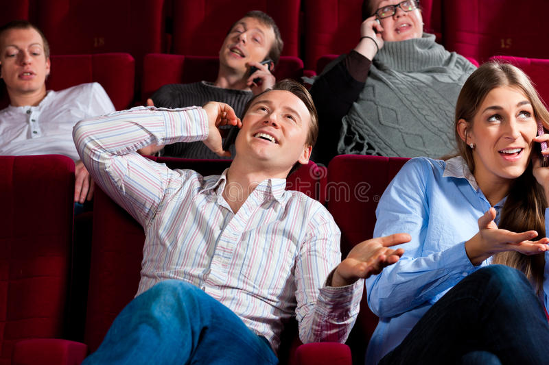 People in cinema theater with mobile phone. Couple and other people, probably friends, in cinema watching a movie, everybody is making a phone call, it seems to stock images