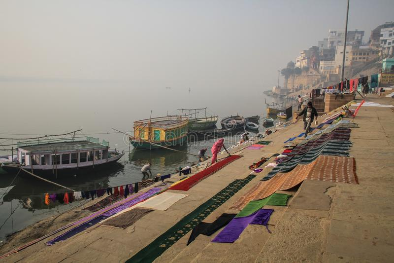 People cleaning laundry early morning on the ganga ghats in Varanasi, Uttar Pradesh, India royalty free stock image