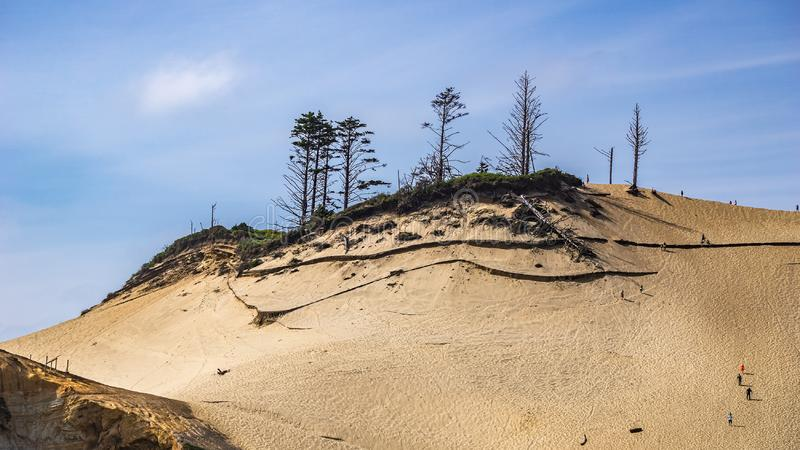 People climbing the huge sand dune at Cape Kiwanda natural state Area, Pacific City on a sunny day, OR, USA. People climbing the huge sand dune at Cape Kiwanda stock images