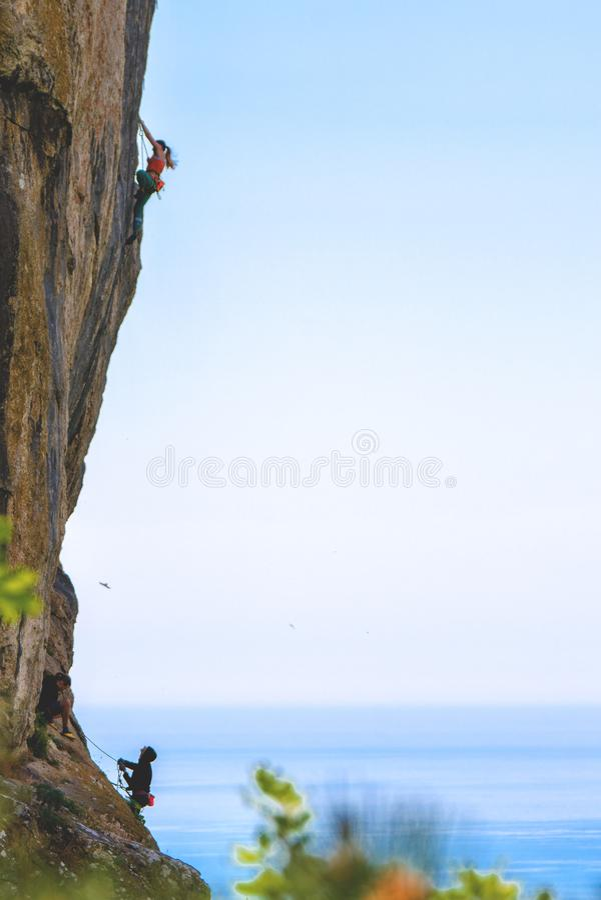 People climbing rock mountain stock photo