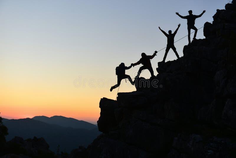 People climbing rock at sunset stock photo