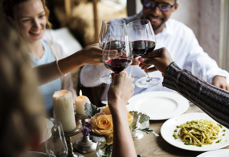 People Clinging Wine Glasses Together in Restaurant stock photography