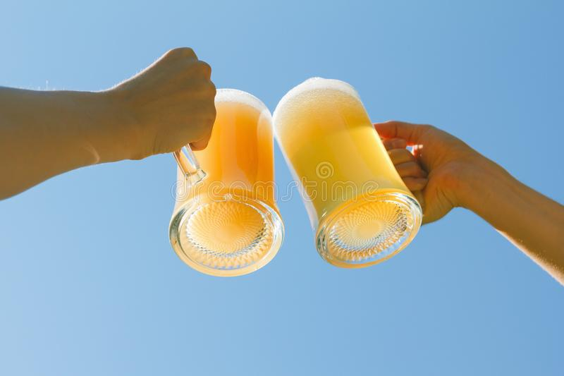 People clink beer. People clink sky sun octoberfest beer background royalty free stock photography