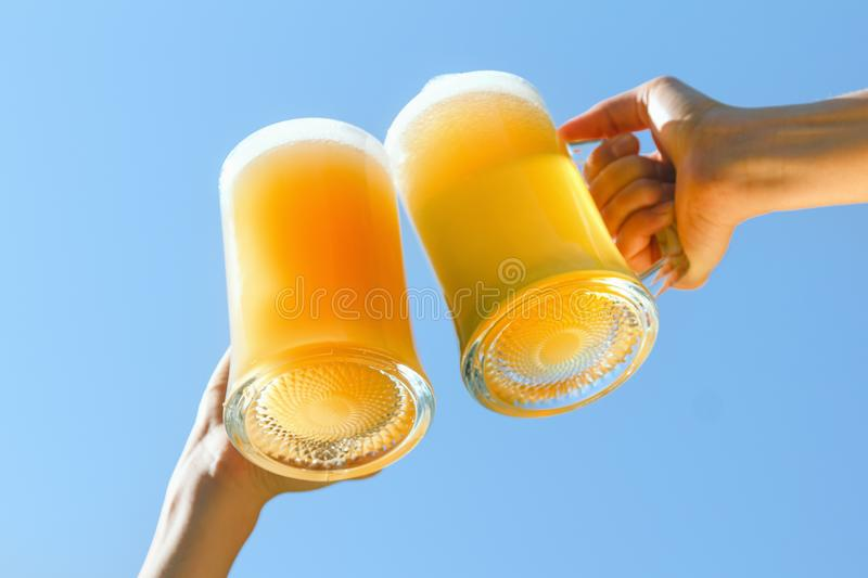 People clink beer. People clink sky sun octoberfest beer background nature blue royalty free stock photo