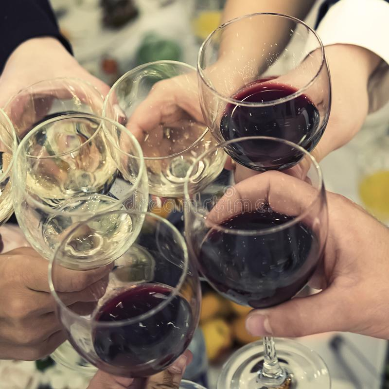 People clinking glasses above reataurant dinner table at some festive occasion. Drinking toasts and clinking tumblers at a dinner royalty free stock photos