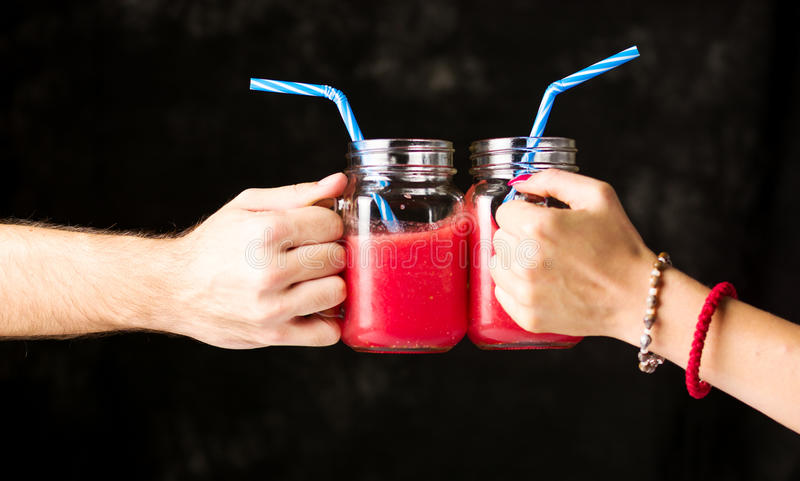 People clinking glasses with watermelon smoothie stock photos