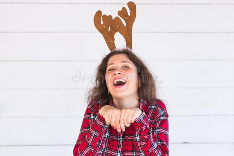 People, holidays and christmas concept - funny santa girl in deer horns on her head on white background stock images