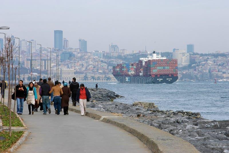 People on the coast and large ship on Bosphorus royalty free stock photo