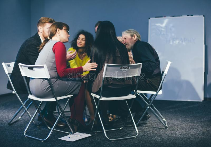 Group therapy session sitting in a circle. People comfort and support each other during group session with professional therapist. Toned concept royalty free stock images