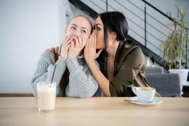People communication and friendship concept - smiling young women drinking coffee or tea and gossiping at outdoor cafe stock image
