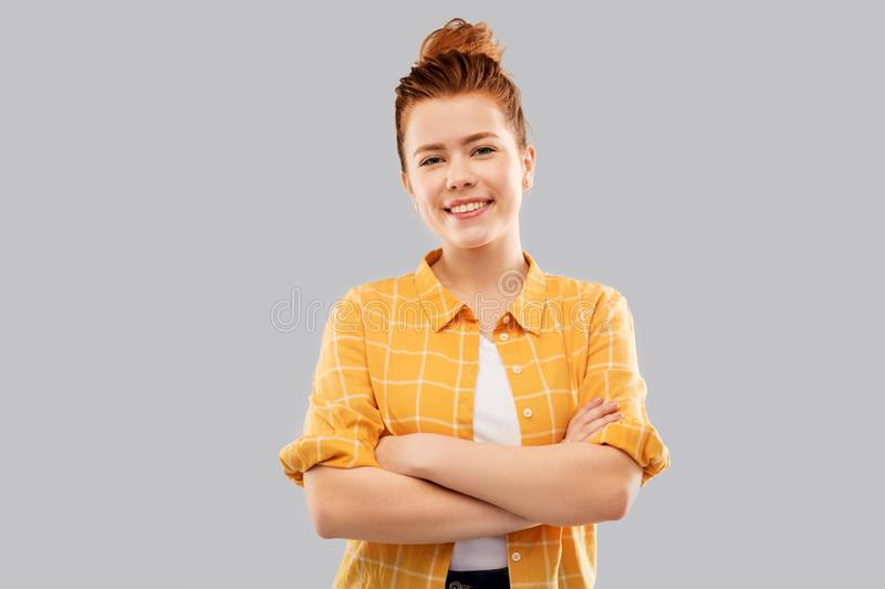 Smiling red haired teenage girl with crossed arms royalty free stock images