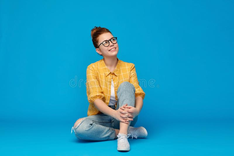 Redhead teenage student girl in glasses dreaming royalty free stock image