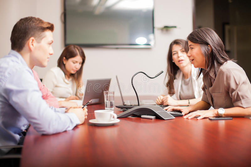 People on a conference call. Group of people talking to a microphone over a conference call at work stock photos