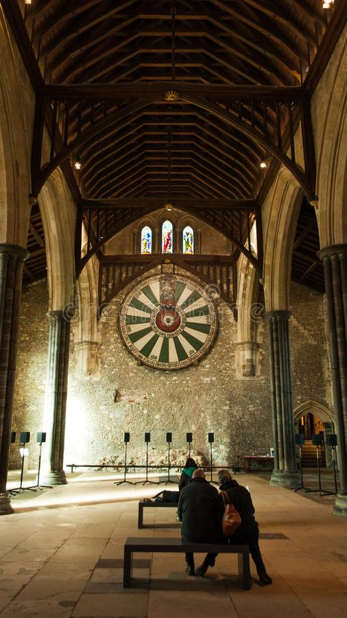People contemplating King Arthur Round table in Winchester Great Hall, UK royalty free stock image