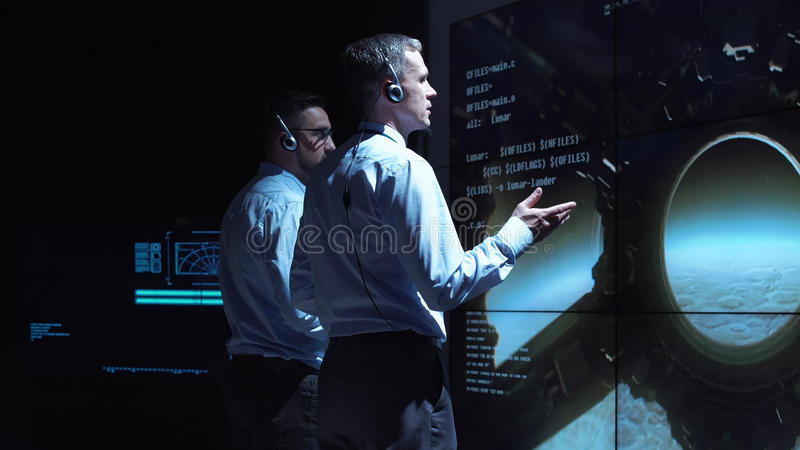 People controlling Moon landing. Back view of two supervisors standing at screen in center and controlling landing on Moon royalty free stock photos