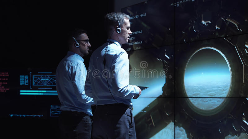 People controlling Moon landing. Back view of two supervisors standing at screen in center and controlling landing on Moon royalty free stock image
