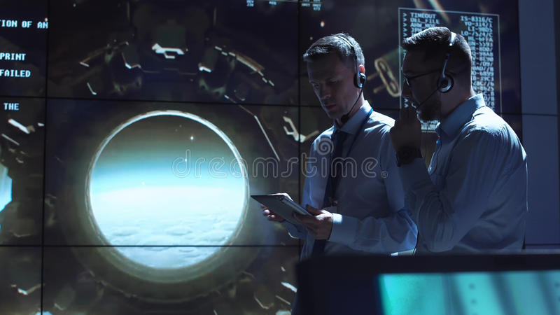 People controlling Moon landing. Two employees control the spacecraft`s flight to the moon stock photos