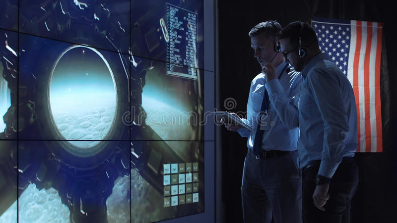 People controlling Moon landing. Two employees in headphones in the control center of flights discuss the flight of the spacecraft to the moon and control its stock photo