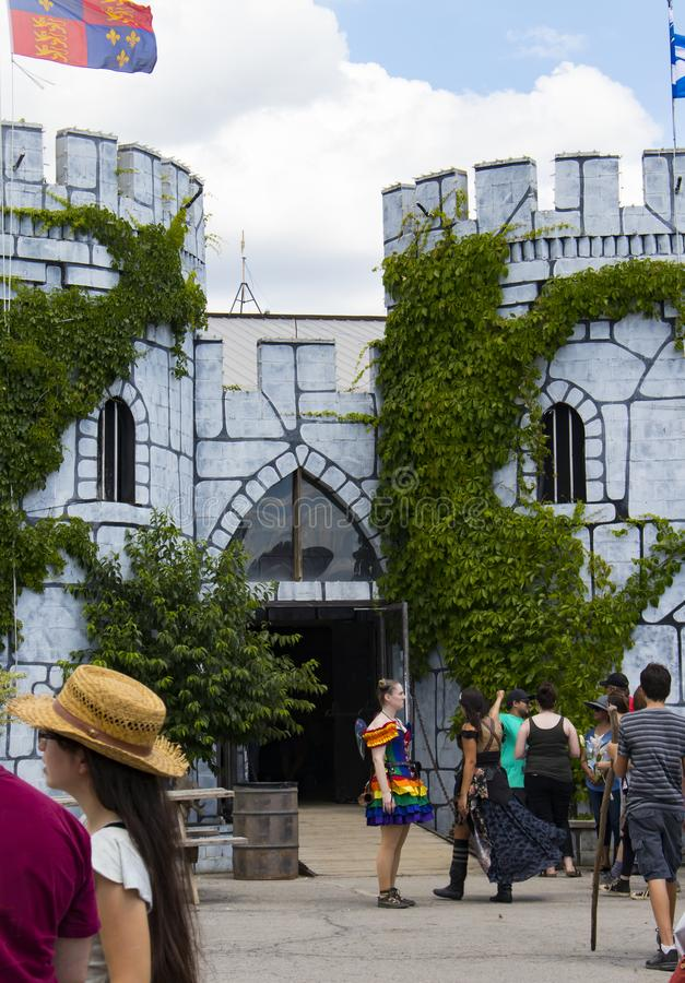 People in costume gathered around the castle entrance including a girl dressed as a rainbow fairy at the Renassiance Festival in M royalty free stock photos