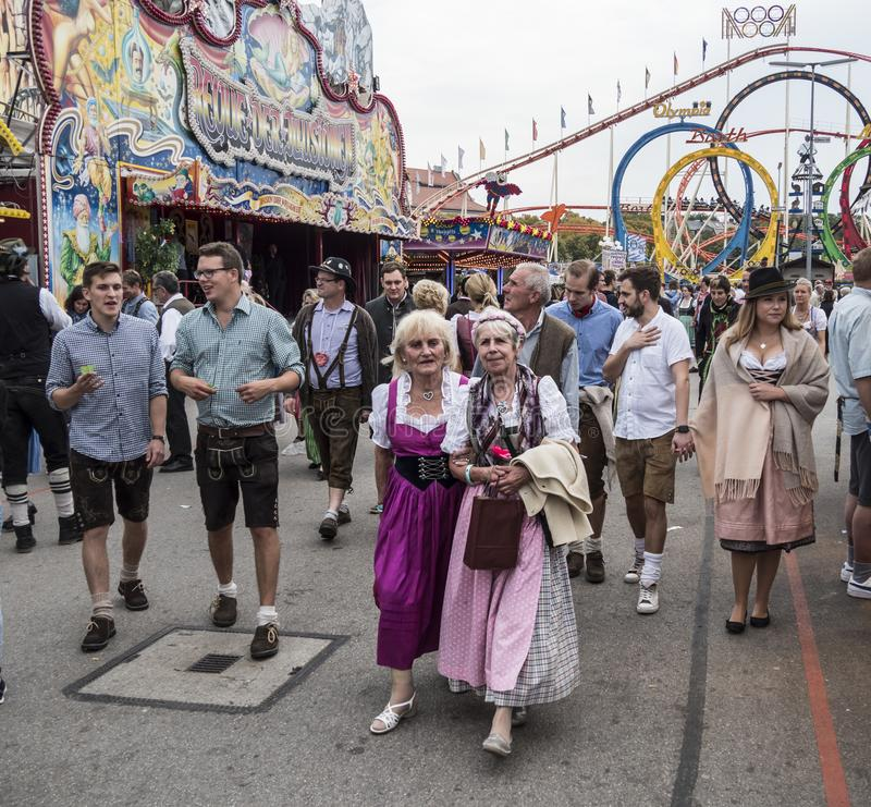 People in costume at the Oktoberfest. People in costume and elderly people in front of the attractions and amusement rides of the Oktoberfest, Munich, Germany stock photography