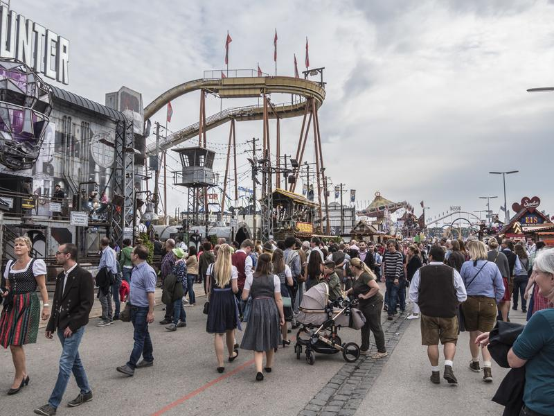 People in costume at the Oktoberfest. People in costume in front of the attractions and amusement rides of the Oktoberfest, Munich, Germany stock photos