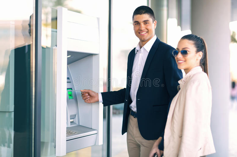 People with credit card standing next to the ATM to withdraw money royalty free stock photo