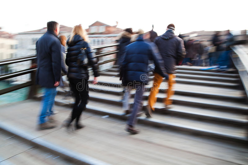 People crossing a bridge in Venice. People crossing the Ponte dell Accademia in Venice, shown in motion blur. The picture was taken by panning the camera stock photo