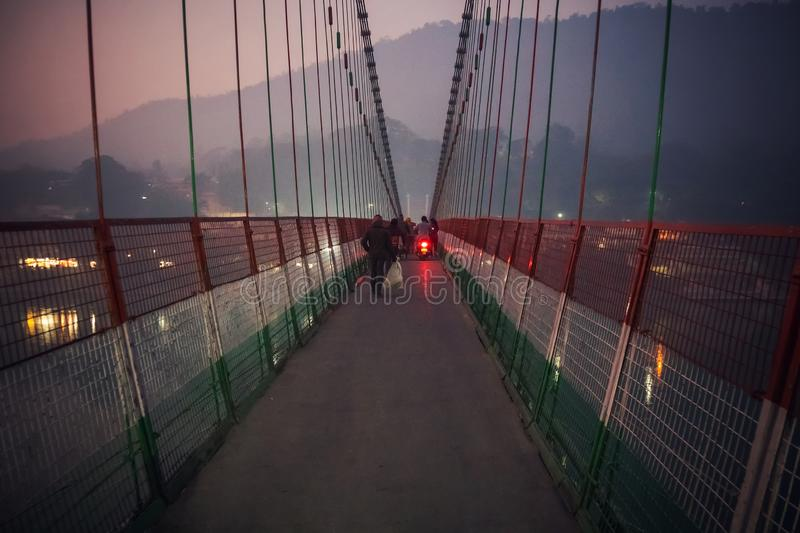 People crossing Laxman Jhula suspension bridge on river Ganga. Night, evening, dark, twilight stock photo