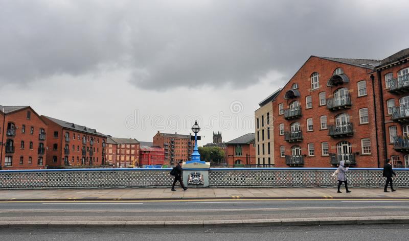 People crossing Leeds bridge with residential building on either side of the river aire. stock image