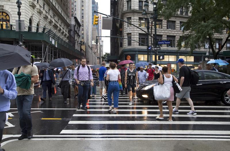 People crossing New York City street during rain royalty free stock photography