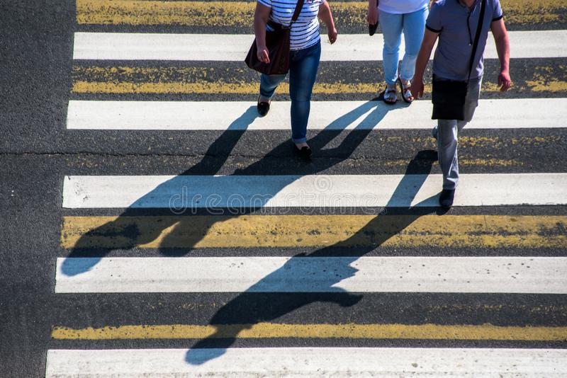 People on crossing. People and their long shadows on pedestrian crossing stock images