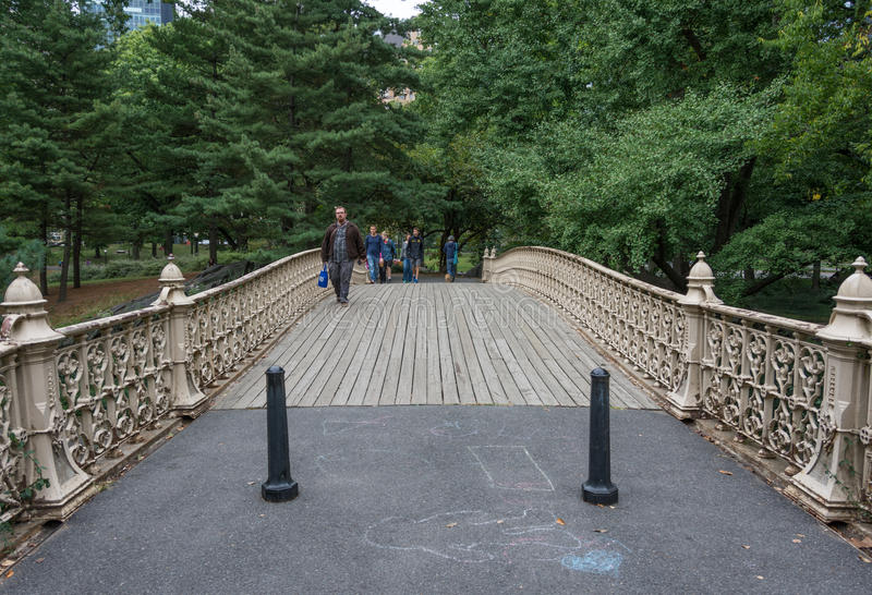 People crossing the Pinebank Arch bridge in Central Park stock photo