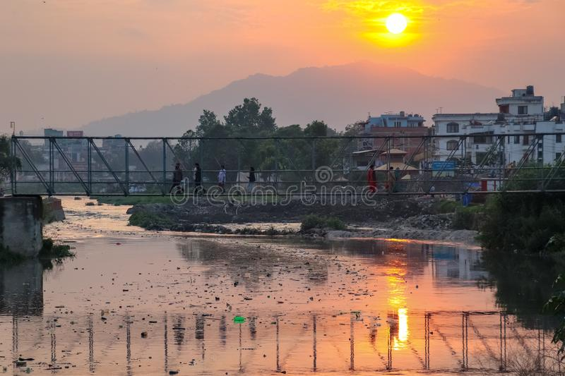 Sunset and polluted river. People crossing polluted river during sunset royalty free stock photos