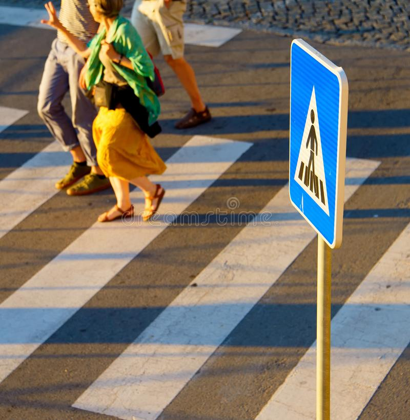 Crosswalk sign. People on background stock photography