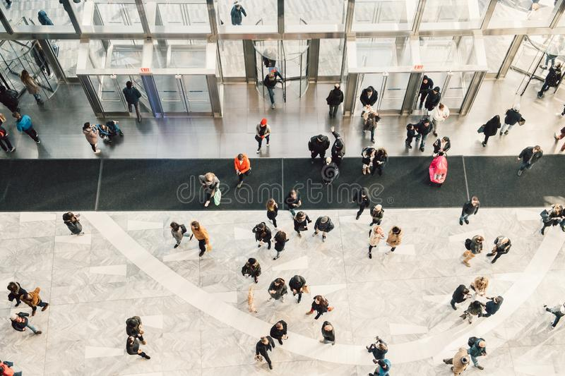 People crowd walking in the business centre and shopping mall entrance. View from the top. stock photo