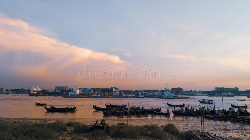 People crowed at Avoymitra Ghat, Chittagong in Bangladesh. Boat, water, ship, mills, grass stock images