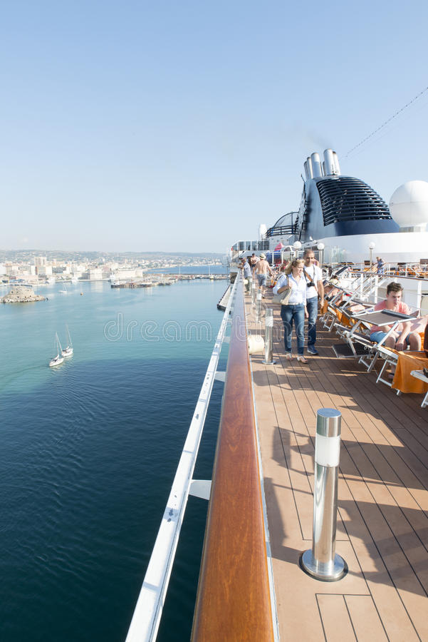People on a cruise ship deck. People enjoying a cruising vacation on the deck of MSC Musica. The MSC Musica is the first Musica-class cruise ship built in 2006 stock photo