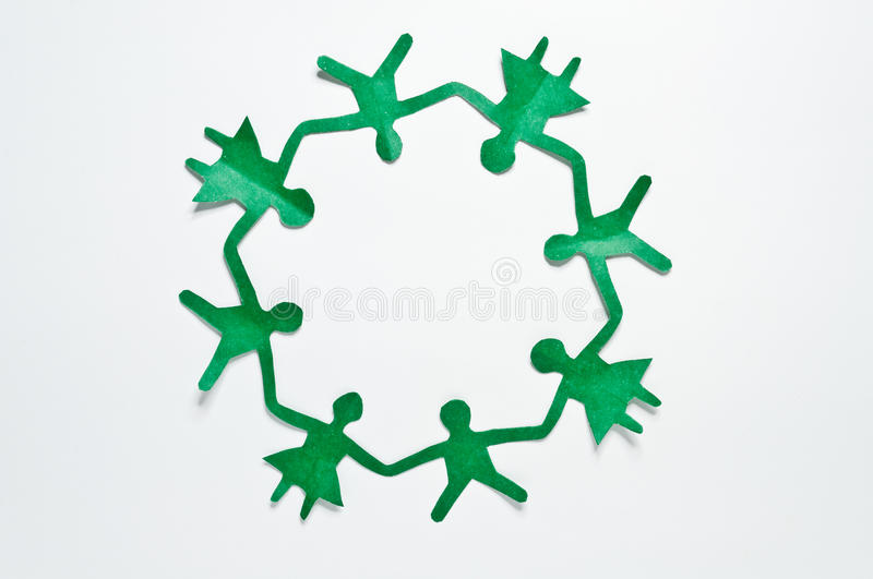 People cut out of paper. Close up of people cut out of green paper on white background royalty free stock photography