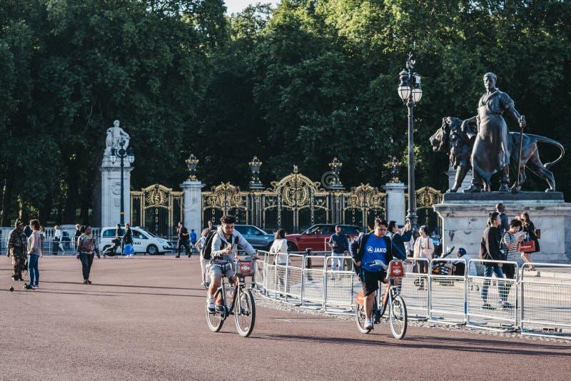 People cycling outside Buckingham Palace, London, UK royalty free stock images