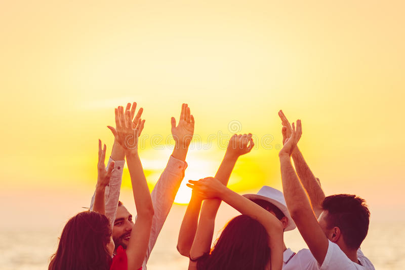 People dancing at the beach with hands up. concept about party, music and people.  royalty free stock photo