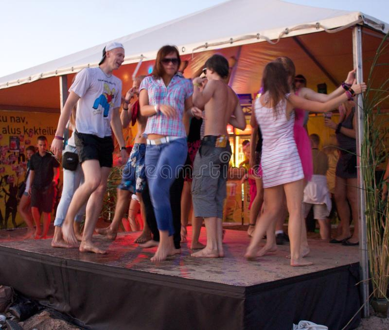 People dancing at beach on stage. Salacgriva, LATVIA - JULY 16 2010: People dancing at beach chill out zone at Positivus Festival 2010 July 16, 2010 in royalty free stock photography