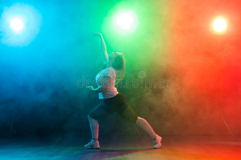People, dancing and jazz funk concept - European young woman demonstrates flexibility over colored background royalty free stock photography