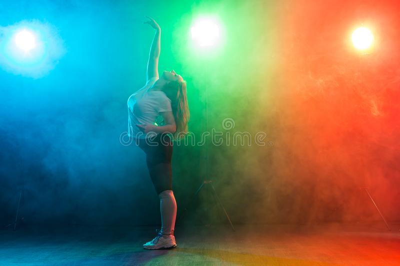 People and dancing concept- European young woman dancing jazz funk over colored background royalty free stock photography