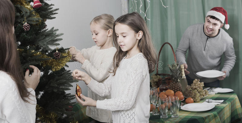 People decorating Christmas tree stock image